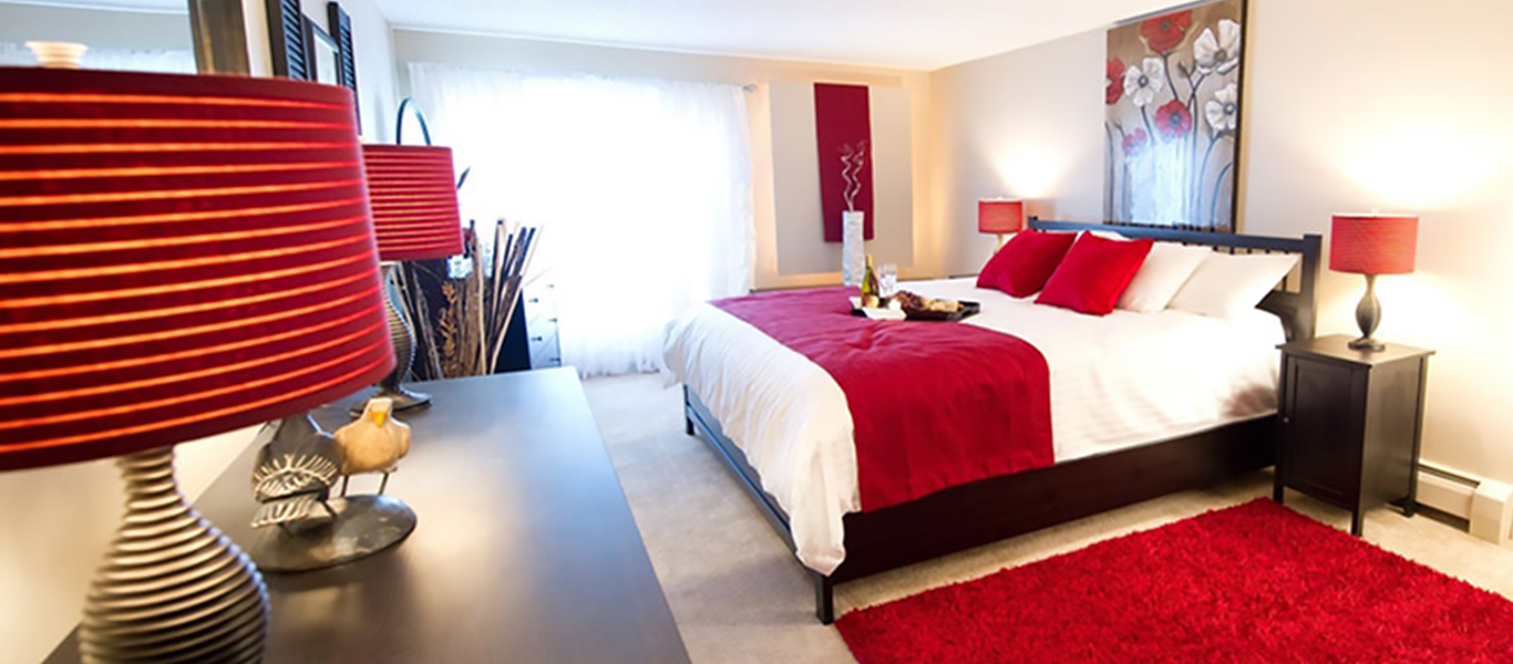 Decorated apartment bedroom with red and white color scheme